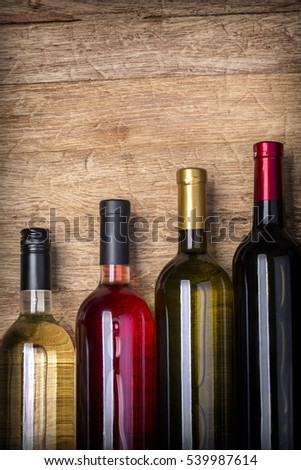 Different bottles of wine on table wooden background  close-up