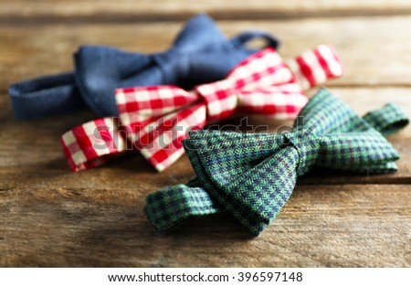 Different bow ties on wooden background - stock photo