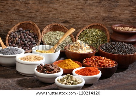 Different bowls of spices over a wooden background - stock photo