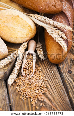 Different bread and wheat on the wooden table