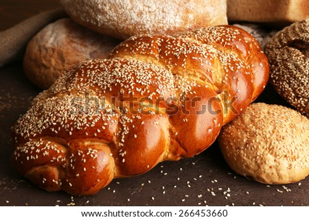 Different bread on wooden background - stock photo