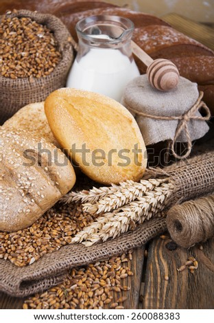 Different bread, wheat, milk and honey on the wooden table