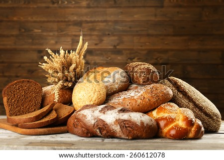 Different bread with ears on wooden background - stock photo