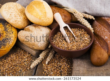 Different bread with wheat on the wooden background