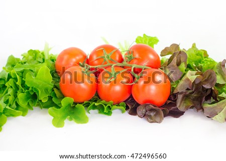 Different bright vegetables on a white background. Tomato and lettuce.