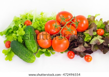 Different bright vegetables on a white background. Tomato, cucumber and lettuce.