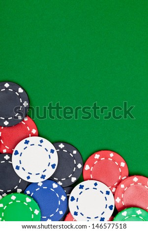 Different casino chips on green table background with copyspace - stock photo