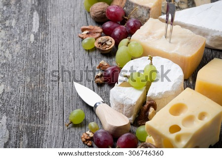 different cheeses, grapes and walnuts on a wooden background, horizontal - stock photo