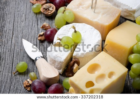 different cheeses, grapes and walnuts on a wooden background, horizontal, close-up