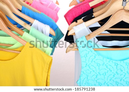 Different clothes on hangers on light background - stock photo
