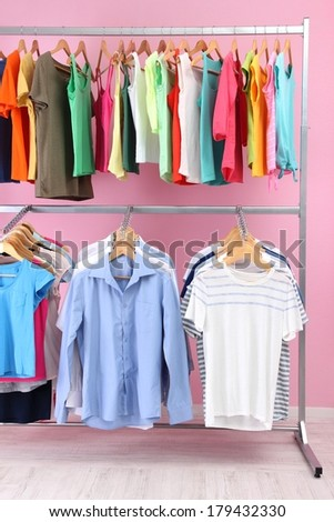 Different clothes on hangers, on pink background - stock photo