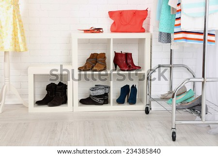 Different clothes on hangers, shoes on shelves in shop - stock photo