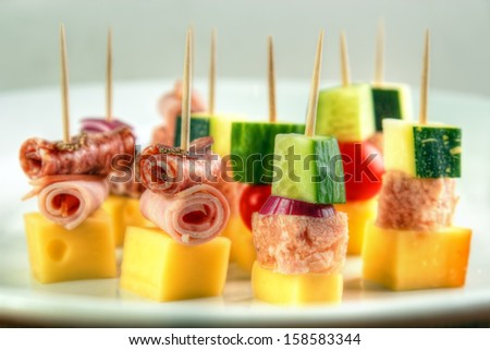 Different cocktail stick snacks , with cheese , zucchini , meat jelly , cucumber and cold cuts rolls - stock photo