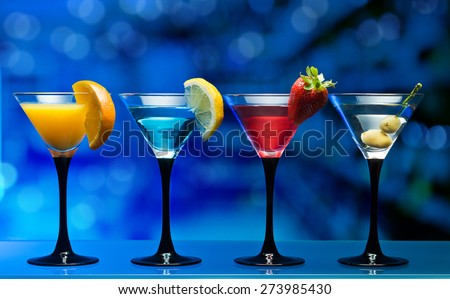 Different cocktails garnished with fruits on glass table in bar - stock photo