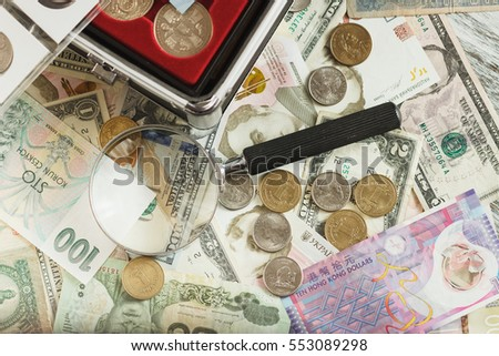Different collector's coins and banknotes with a magnifying glass, soft focus background