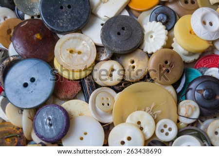 Different color buttons in whites, neutrals, blues and blacks piled for a great color, retro style background.   - stock photo