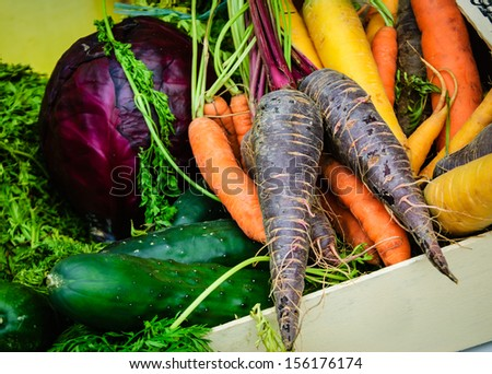 Different color carrots, red cabbage and cucumbers in wooden box. Fresh organic produce from a local farmers market in Paris. - stock photo