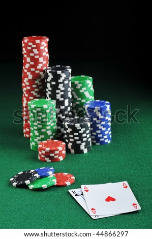different color chips for gambling and playing cards on green - stock photo