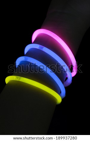 Different color glow stick bracelets on hand - stock photo