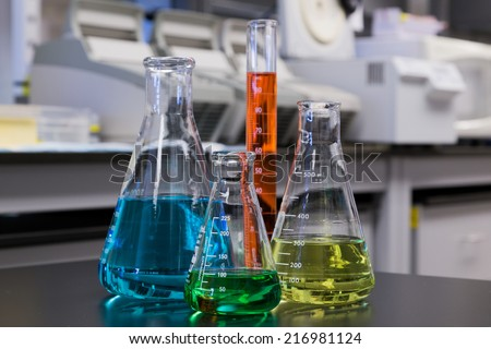 Different color liquids in flasks and a measuring cylinder with a laboratory background.