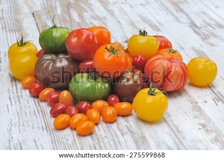 different color varieties of tomatoes on a wooden white table - stock photo