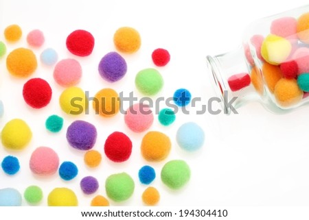 Different colored candy of varying sizes spill from a glass jar. - stock photo