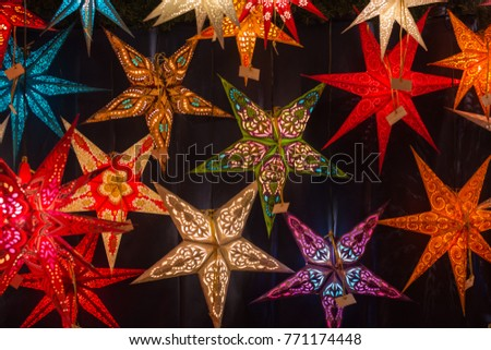 Different colored Christmas stars at a Christmas market close up