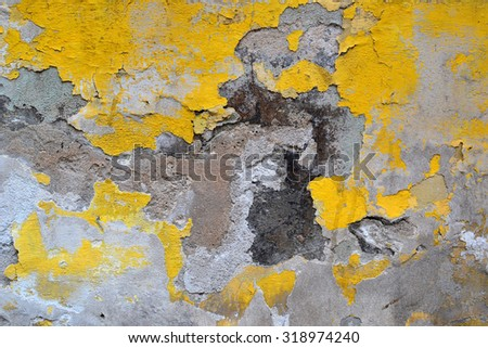 Different colored cracked yellow plaster wall.Cracks in the plaster.