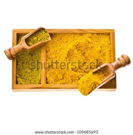 Different colored ground spices powders and solid with wooden spoons in a wooden box isolated on a white background