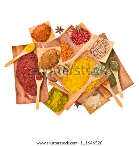 Different colored ground spices powders and solid with wooden spoons in a wooden coasters  isolated on white background