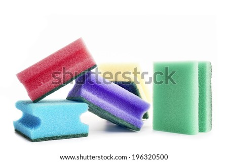 Different colored sponges on white background