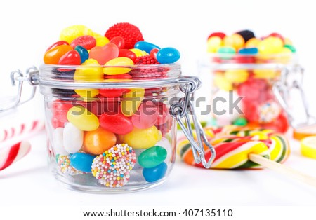 different colorful candy, sweetmeats and chewing gum in the jar of glass close-up on a white background with space for your text