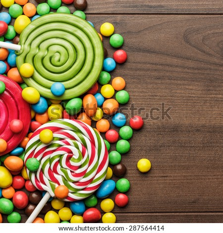 different colorful sweets and lollipops on the wooden table - stock photo