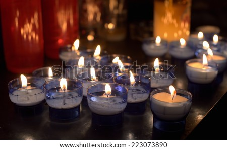 Different colors firing candles in catholic church on dark background - stock photo