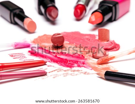 Different colors of smeared and sliced lipstick, lip gloss with brushes, lip liner on white textured surface. Shallow depth of field. Focus on the right brush - stock photo