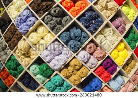 Different colors wool balls on shop display stand for sale - stock photo