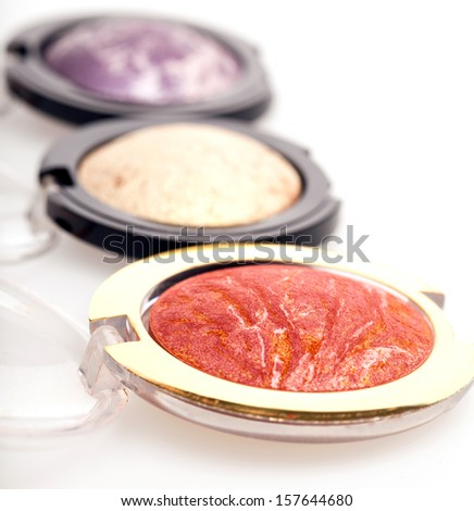 Different colours of eye shadow in individual compacts arranged in a receding row with shallow dof, foremost color is red in a gold metallic compact - stock photo