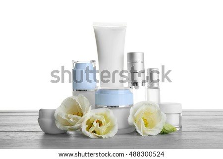 Different cosmetic bottles and eustoma flowers on table