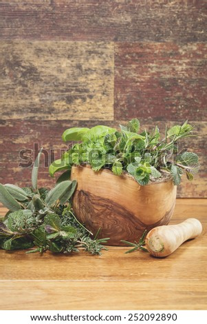 Different culinary herbs in a mortar over rustic table. A macro photograph with  shallow depth of field.