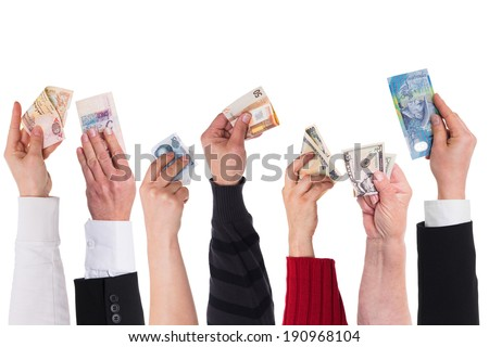 different currencies holding by different hands - stock photo