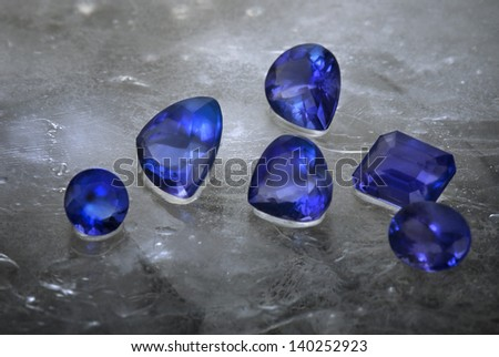 Different cuts of Tanzanite isolated on grey ice background.