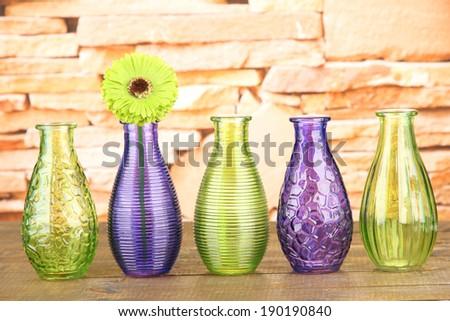 Different decorative vases on shelf on brick wall background - stock photo
