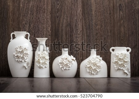 Different decorative white vases with 3d flower and butterfly designs