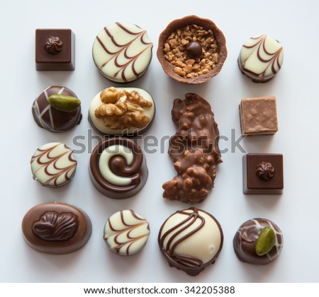 Different delicious white and milk chocolate pralines on white plate, selective focus - stock photo