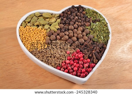 Different dry spices in plate in the form of heart - stock photo