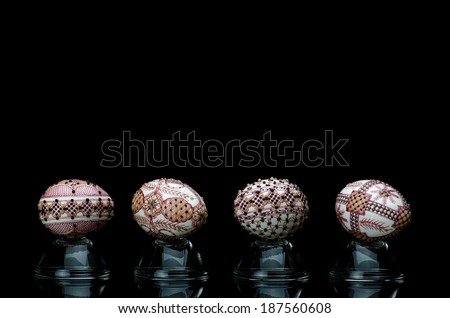 Different Easter eggs presented on small glass against black background