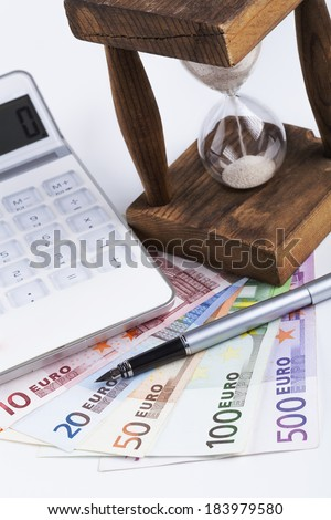Different euro banknotes with hourglass white calculator and silver fountain pen on white background