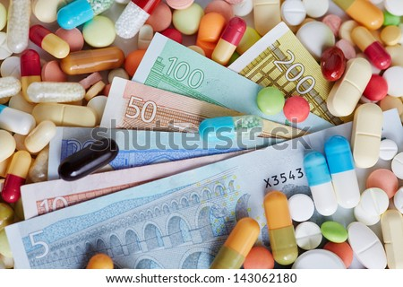 Different Euro money bills on pills and colorful medicine - stock photo
