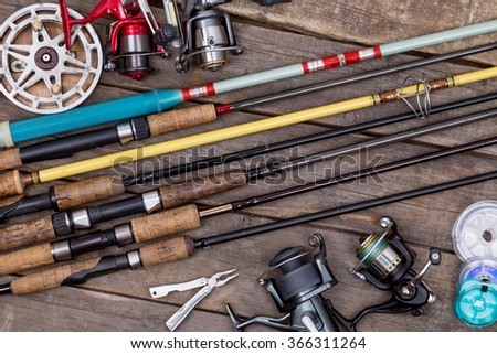 different fishing rods and reels on wooden boards background. creative idea for design tackle service, repair. - stock photo