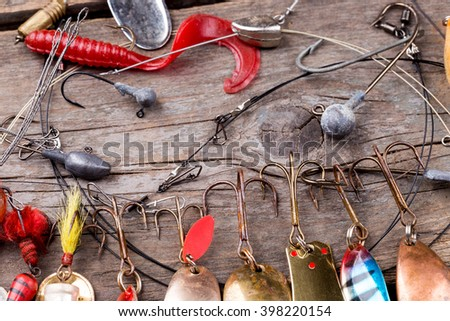 different fishing tackles and spoon on wooden board background. Concept design for freshwater outdoor active business company.